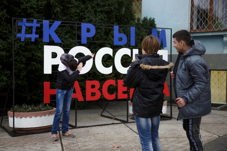 "The song men take photos near the sign ""Crimea - Russia - Forever"" installed on Lenin square near the Council of Ministers of the Republic of Crimea on Oct. 14 in Simferopol."